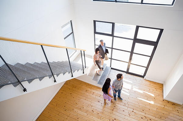 Real estate agent showing open house to family
